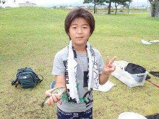 外来魚に触れる少年
